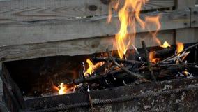 Heldere oranje brandbrandwonden in een zwarte metaalgrill met brunches stock video