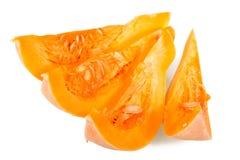 Heldere oranje die plakken van pompoen met zaden op wit worden geïsoleerd Stock Foto's