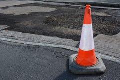 Heldere oranje en witte verkeerskegel op een stoep royalty-vrije stock afbeelding