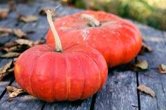 Heldere oranje pompoenen op een oude houten lijst met droge de herfstbladeren royalty-vrije stock afbeeldingen