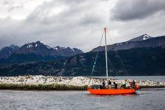 heldere oranje zeilboot die het brakkanaal, met rotsachtige die eilanden bezoeken door aalscholvers worden gewoond in Ushuaia, Ar royalty-vrije stock afbeelding
