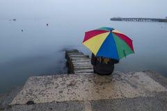 Heldere paraplu met meisje op strand met mist Royalty-vrije Stock Afbeeldingen
