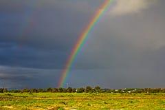 Heldere regenboog voor donkere onweerswolken stock foto's