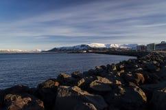 Heldere Reykjavik tegen de achtergrond van de pieken van de zasnezhenyhberg stock fotografie
