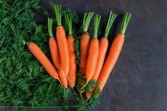 Heldere rijpe wortelen met bladeren op de lijst stock foto