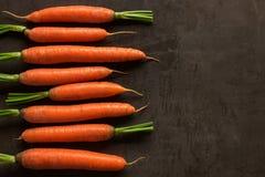 Heldere rijpe wortelen met bladeren op de lijst royalty-vrije stock foto's