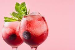 Heldere rode alcoholische schoten in twee wijnglazen met bosbes, ijsblokjes, groene muntclose-up, hoogste sectie over pastelkleur royalty-vrije stock foto