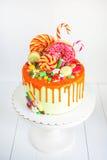 Heldere rode die verjaardagscake met snoepjes, suikergoed, doughnut, suikergoed, marmelade wordt verfraaid Stock Afbeeldingen