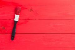 Heldere rode geschilderde houten oppervlakte met borstel Stock Foto's