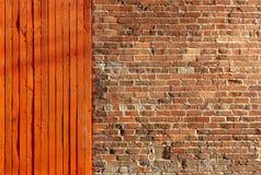 Heldere rode houtomheining naast een oude bakstenen muur royalty-vrije stock afbeelding