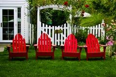 Heldere rode stoelen in een mooie tuin Stock Foto's