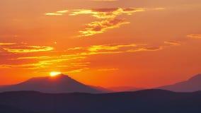 Heldere rood-oranje zonsopgang achter de berg stock footage