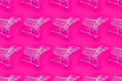 Heldere roze achtergrond met een karretje voor de supermarkt stock fotografie