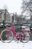 Heldere roze fiets op de brug dichtbij het kanaal in Amsterdam Royalty-vrije Stock Afbeelding