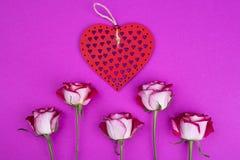 Heldere rozen met een rood houten hart Stock Fotografie