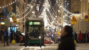 Heldere trams op centrale straten in Helsinki tijdens Kerstmis Heel wat mensen, vakantieverkoop en heldere decoratie stock footage