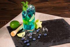 Heldere verfrissende blauwe lagunecocktail met plakken van kalk, ijs, bosbessen en carambola, op het zwarte lijst-servet De ruimt Royalty-vrije Stock Foto's