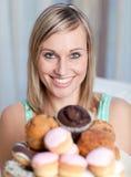 Heldere vrouw die een plaat van cakes houdt Royalty-vrije Stock Afbeelding