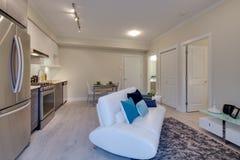 Heldere woonkamer met keuken en dinerlijst Stock Foto's