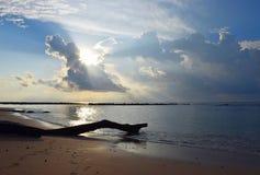 Heldere Zonnestralen van Gouden Zon die door Wolken in Sunny Sky over Zeewater en een Houten Logboek komen royalty-vrije stock afbeeldingen