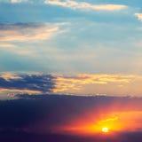 Heldere zonsondergang en hemel met donkere wolken Stock Fotografie