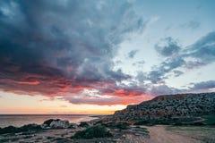 Heldere zonsondergang op een rotsachtige oceaankust royalty-vrije stock fotografie