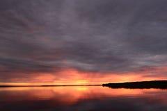 Heldere zonsondergang tegen de achtergrond van een donkere hemel in cirruswolken Stock Foto's