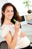 Heldere zwangere vrouw die augurk in haar bureau eet stock foto