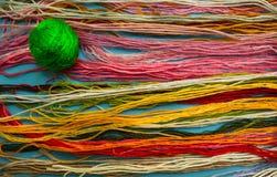 Heldergroene clew op een achtergrond van kleurrijke draden stock fotografie