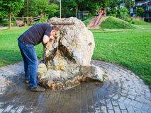 Helenen Quelle fountain in city park of Gerolstein. GEROLSTEIN, GERMANY - JUNE 27, 2010: man drink natural mineral water from Helenen Quelle fountain in city Royalty Free Stock Photos