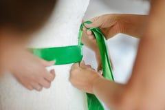 Helfen der Braut, ihr Hochzeitskleid zu setzen stockfoto