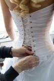 Helfen der Braut mit weißem Korsett der Braut Stockbilder