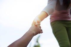Helfen Sie Händen junges Mädchen des Konzeptes, die heraus erreichen, um altes zu helfen Lizenzfreie Stockfotos