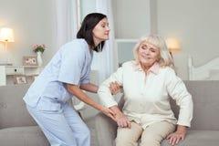 Helfende ältere Frau der anziehenden Krankenschwester stockbilder