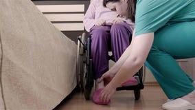 Helfende behinderte Frau des Ältesten der Krankenschwester im Rollstuhl, zum sie in Bett einzusetzen stock footage