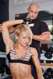 Helfende Blondine des persönlichen Trainers in der Presse von Dummköpfen Stockbild