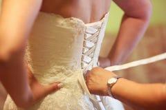 Helfende Braut der Brautjungfer binden ihr Hochzeitskleid Lizenzfreies Stockbild