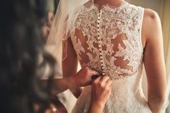 Helfende Braut der Brautjungfer Korsettnahaufnahme und das Erhalten ihres Kleides, Vorbereitungskonzept befestigen am Morgen für  stockfotos