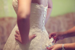 Helfende Braut der Brautjungfer, zum ihres Kleides zu binden Stockfotografie