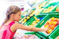 Helfende Eltern, die Früchte kaufen Lizenzfreie Stockfotografie