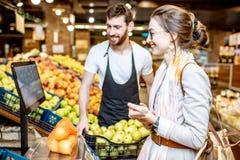 Helfende Frau der Arbeitskraft, zum von Früchten im Supermarkt zu wiegen stockfotos
