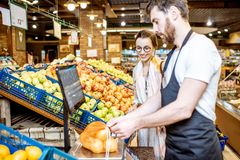 Helfende Frau der Arbeitskraft, zum von Früchten im Supermarkt zu wiegen lizenzfreies stockfoto