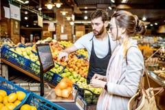 Helfende Frau der Arbeitskraft, zum von Früchten im Supermarkt zu wiegen lizenzfreies stockbild
