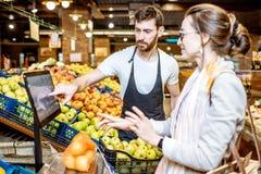 Helfende Frau der Arbeitskraft, zum von Früchten im Supermarkt zu wiegen lizenzfreie stockfotografie