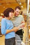 Helfende Frau des Verkäufers, die Lebensmittelgeschäfte findet Stockbilder