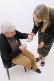 Helfende Großmutter mit ihrer Medikation Stockfoto
