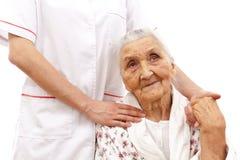Helfende Hand des jungen Doktors für die älteren Stockbild