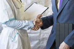Helfende Hand Geschäftsmann, der Hände mit Doktor rüttelt Hände rüttelt Lizenzfreies Stockfoto