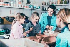 Helfende Jugendliche des Lehrers an der Herstellung von Tonwaren während der Künste und des craf Lizenzfreies Stockbild