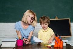 Helfende Kinder des Lehrers mit ihrer Hausarbeit im Klassenzimmer in der Schule vorsch?ler Hausunterricht oder Privatschule lizenzfreies stockbild